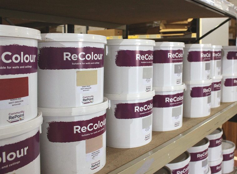 A selection of low cost and eco ReColour emulsion paint on a shelf. There are a range of colours in matt emulsion paint, including Roman Red, Sandy Soles, and Silver Sonnet.