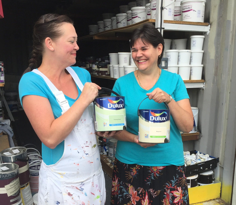 Staff holding paint at Community RePaint Torfaen.