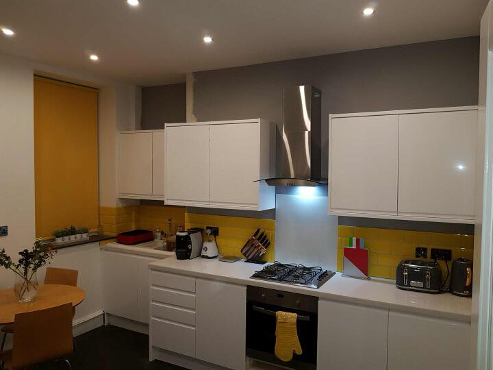 Kitchen redecorated in grey emulsion and yellow tiles.