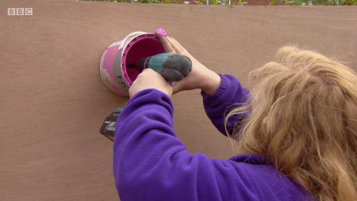 Drilling paint containers onto wooden board