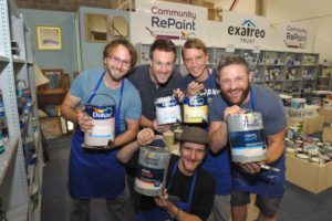 Group photo of staff at Community RePaint Loughborough. Each team member is upholding up a recycled paint container. In the background you can see the paint display which contains a selection of cheap and recycled paint for sale.