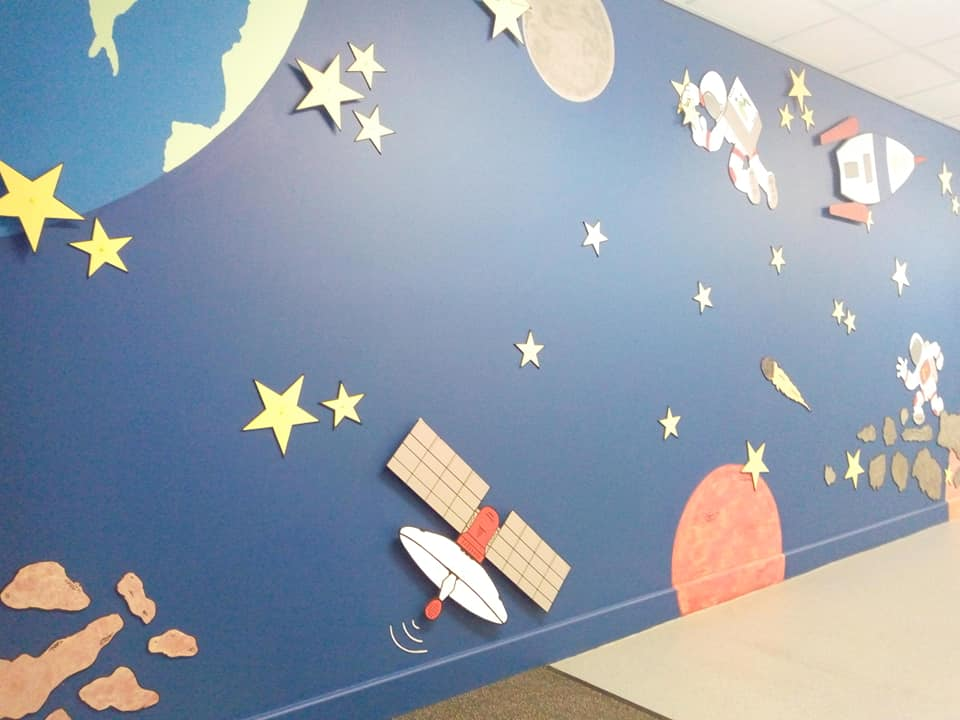 A painted school wall in Bradford using paint from Community RePaint Bradford'sIt shows carefully cut out space shapes from MDF on a background of dark blue and orange silk emulsion paint.