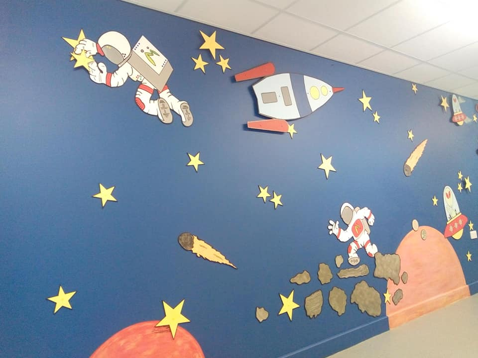 A painted mural at a school in Bradford using paint from Community RePaint Bradford'sIt shows carefully cut out space shapes from MDF on a background of dark blue silk emulsion paint.