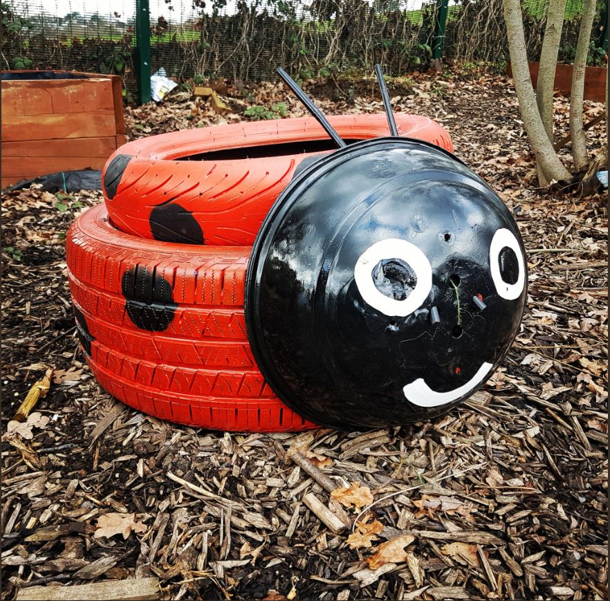 Upcycled car tyre with cheap and reusable paint to make a painted garden planter that looks like a ladybird.