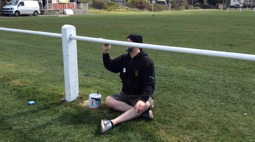 A volunteer painting a fence at Clayton Rugby Club on their community action day with recycled and cheap paint from Community RePaint Bradford.