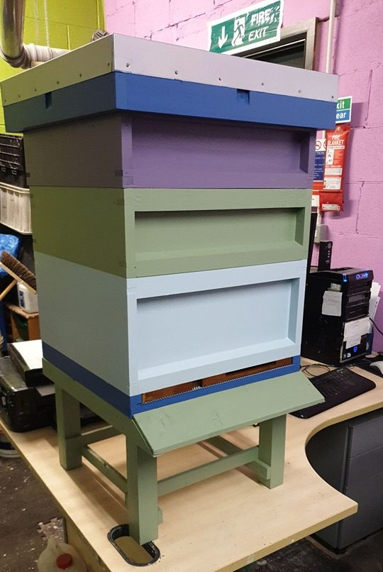 An upcycled painted beehive in pale pink paint, purple paint, green paint and light blue paint using low cost and recycled paint from Community RePaint Bradford.