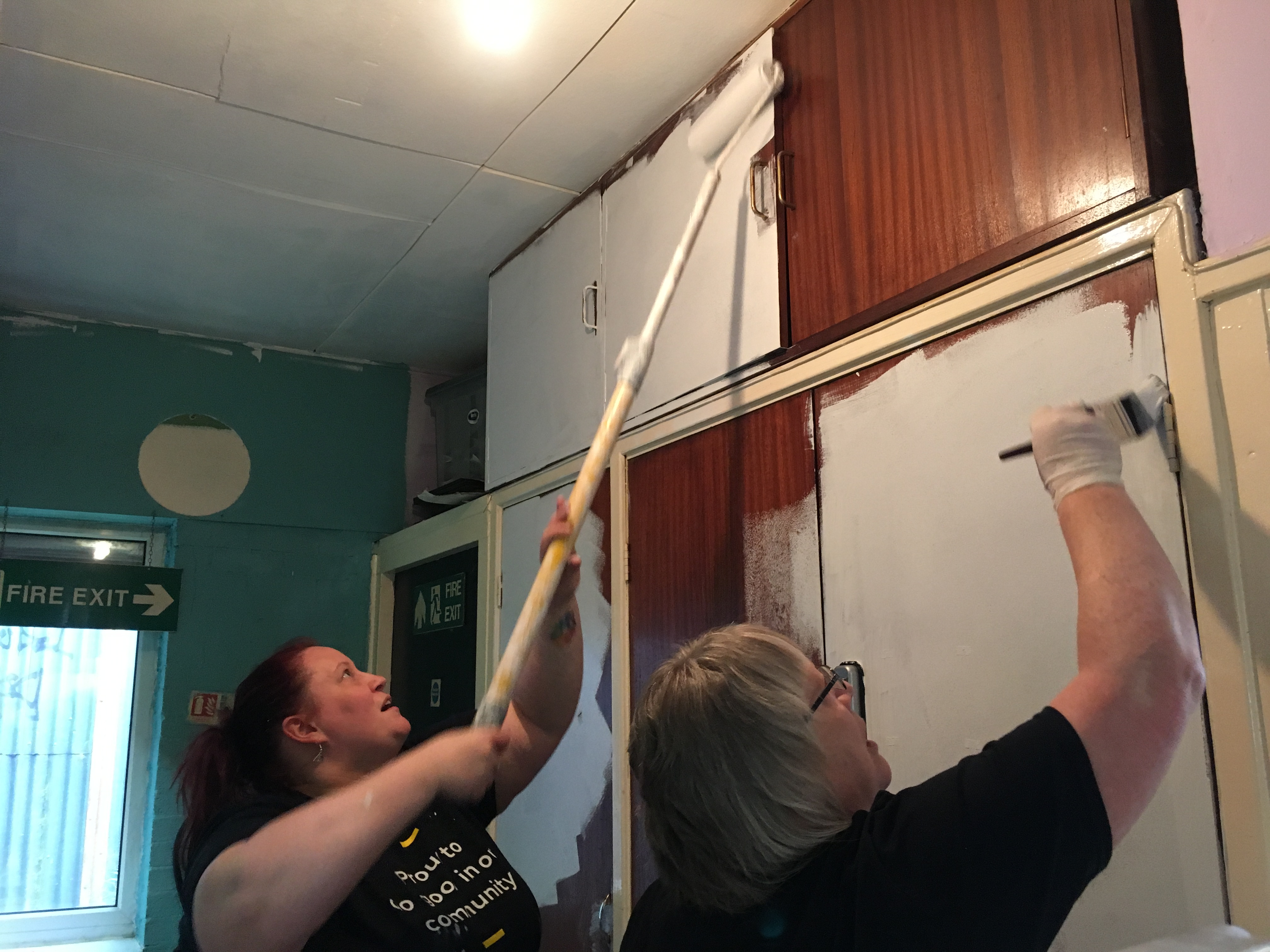 Volunteers painting a cupboard using cheap and recycled paint from Community RePaint Birmingham.