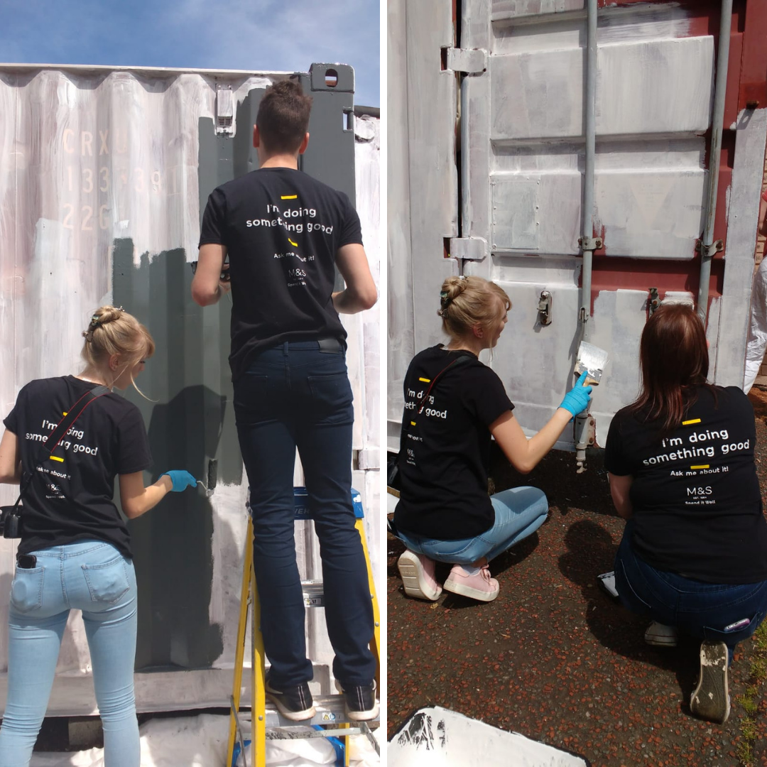 Volunteer team painting a shipping container white, using cheap and eco friendly paint from Community RePaint Torfaen.