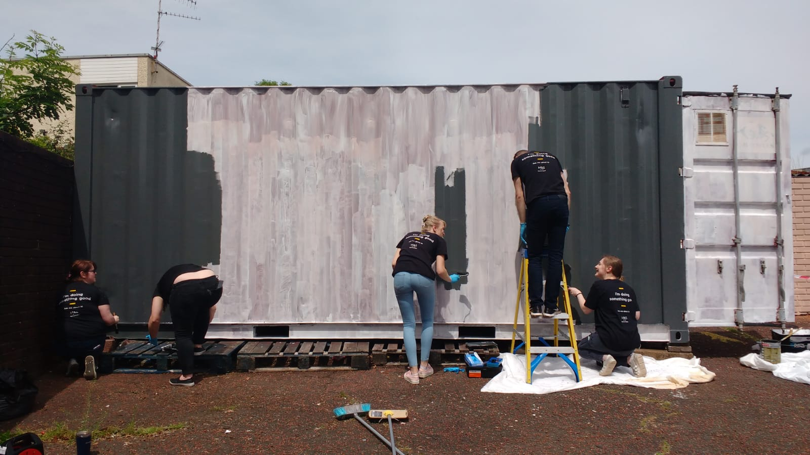 Volunteers painting a shipping container white, using cheap and eco friendly paint from Community RePaint Torfaen.