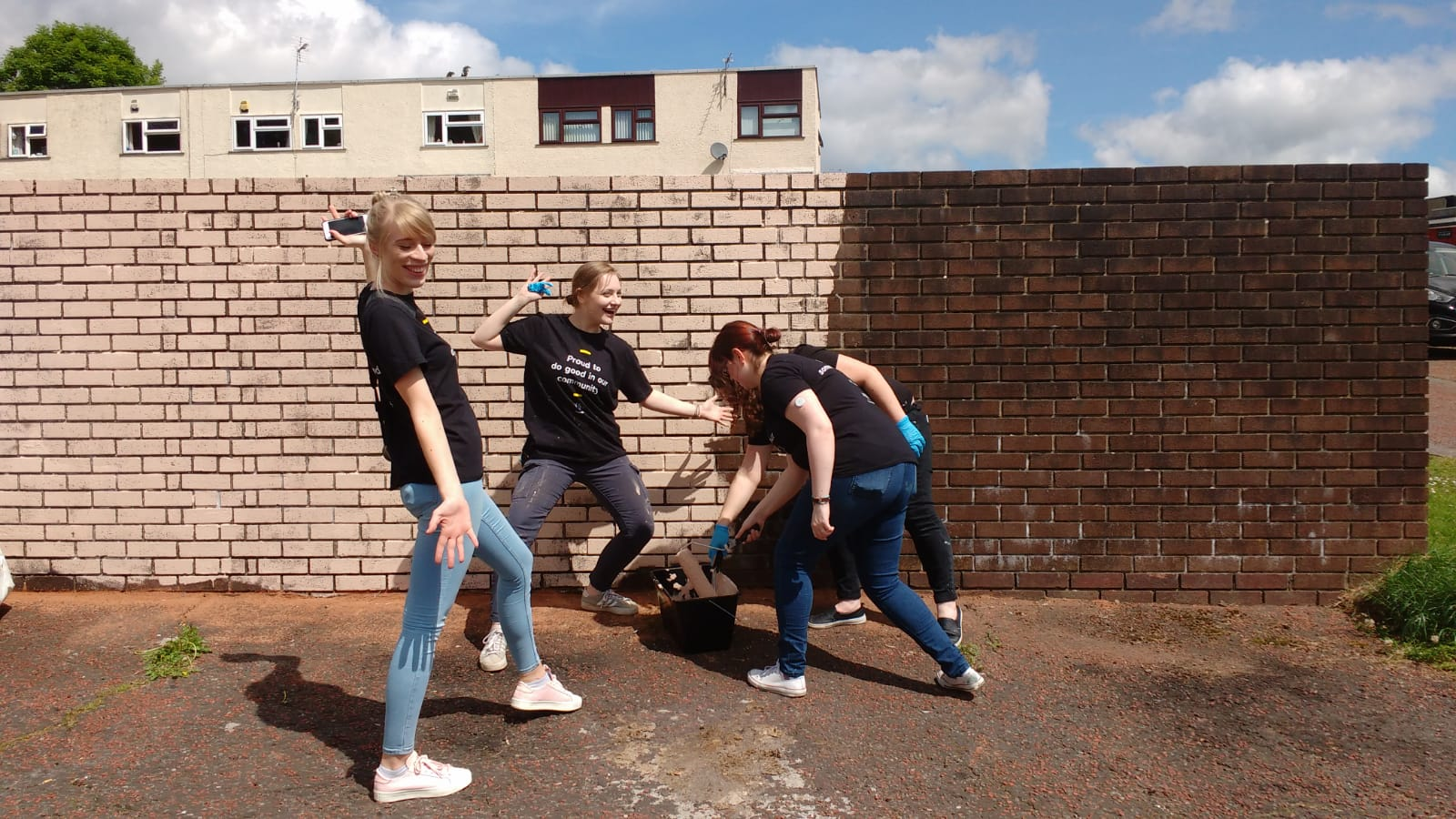 Volunteer team painting a brick wall cream, using cheap and eco friendly paint from Community RePaint Torfaen.