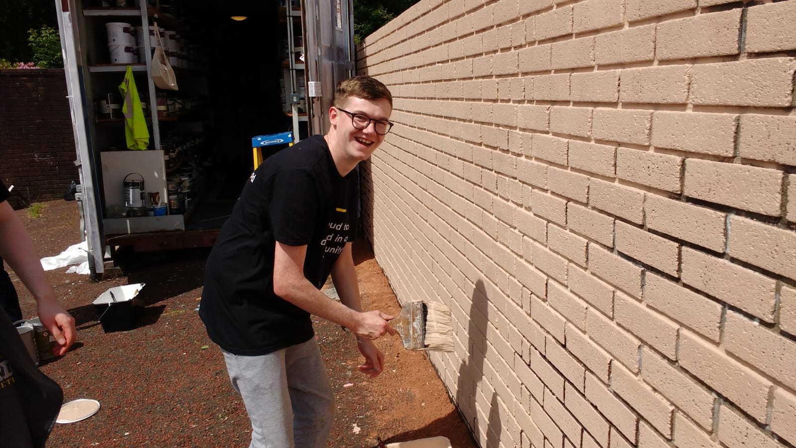 Volunteers painting a brick wall cream, using cheap and eco friendly paint from Community RePaint Torfaen.