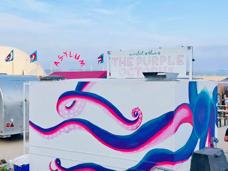 The Scarlet Jade Art painted food truck. The background is white and on top is a large octopus in purple and pink.