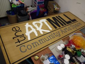 A painted wooden sign that reads: the Artmill Community Arts Space.