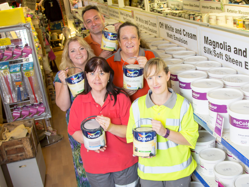 Community RePaint staff in Cambridge who divert leftover paint from the wastestream. All five staff pictured are holding up containers of paint for sale.