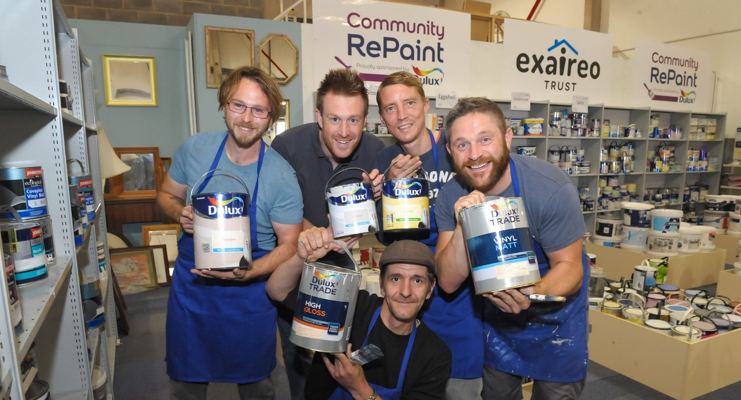 Team photo of staff based at Community RePaint Loughborough holding containers of paint.