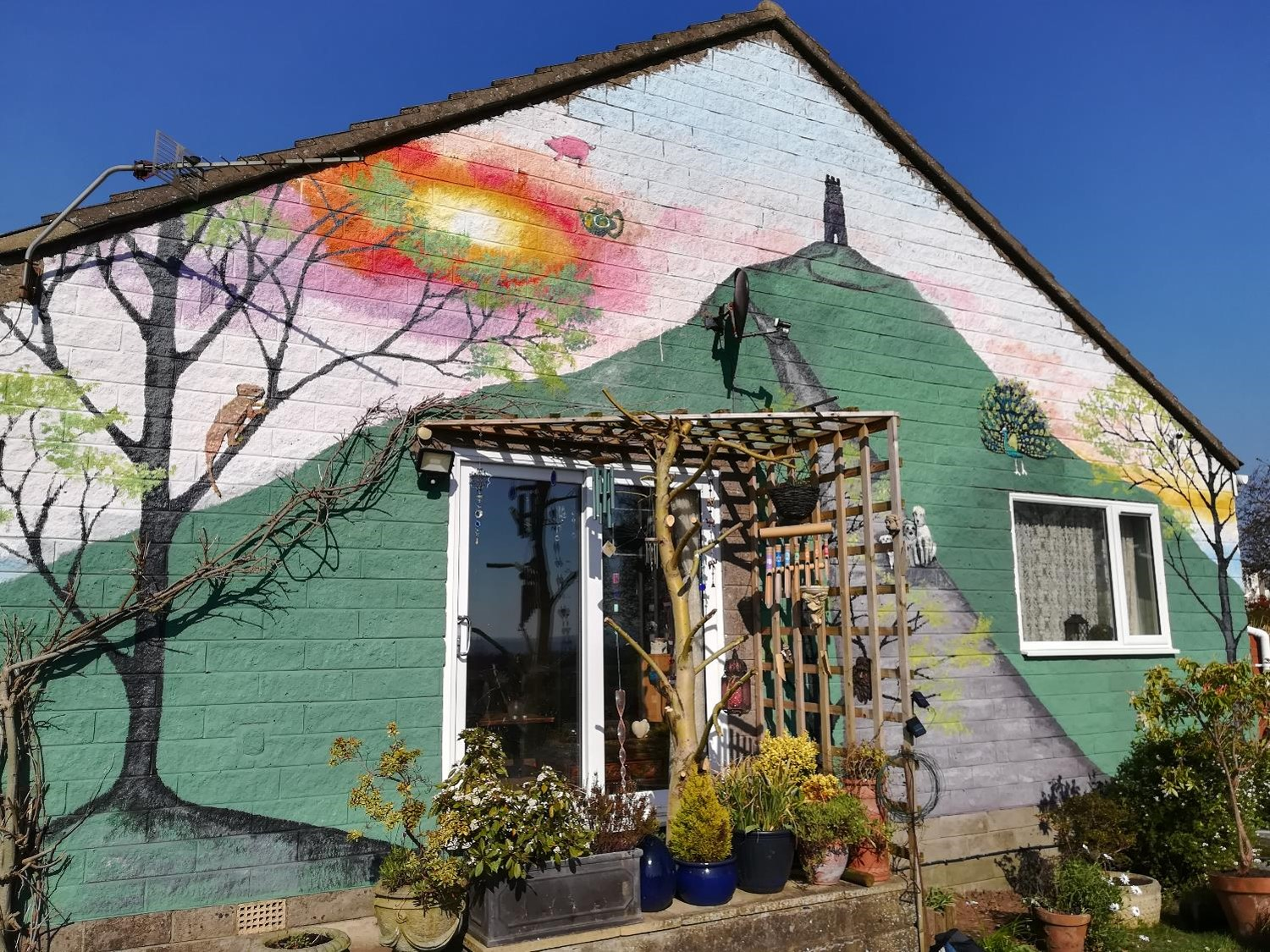 Painted home in Glastonbury featuring a mural of the Glastonbury Tor