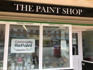 The shop front of The Paint Shop, the Community RePaint Northampton scheme. In the window is the Community RePaint logo and a few paint containers.