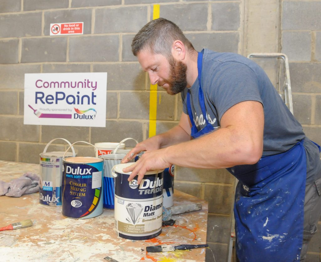 A member of staff at the Community RePaint Loughborough scheme in a workshop processing paint ready for resale. He is in the process of returning a lid to a container of Dulux Trader Diamond Matt.