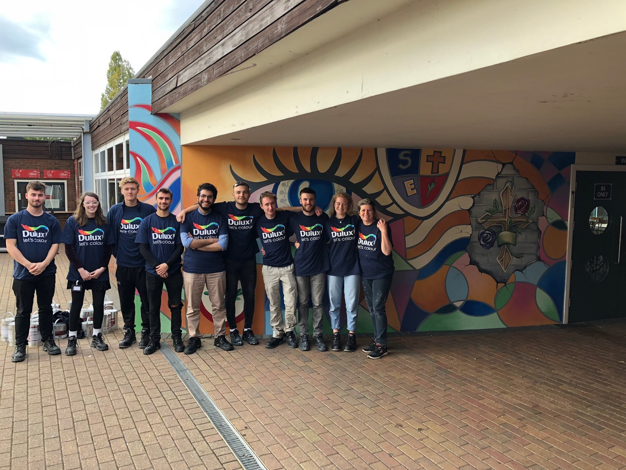A group of 10 volunteers stand next to a newly paint wall that features a brightly coloured mural using cheap and environmentally paint from a Community RePaint scheme. The volunteers are all wearing t-shirts that feature the Dulux logo.