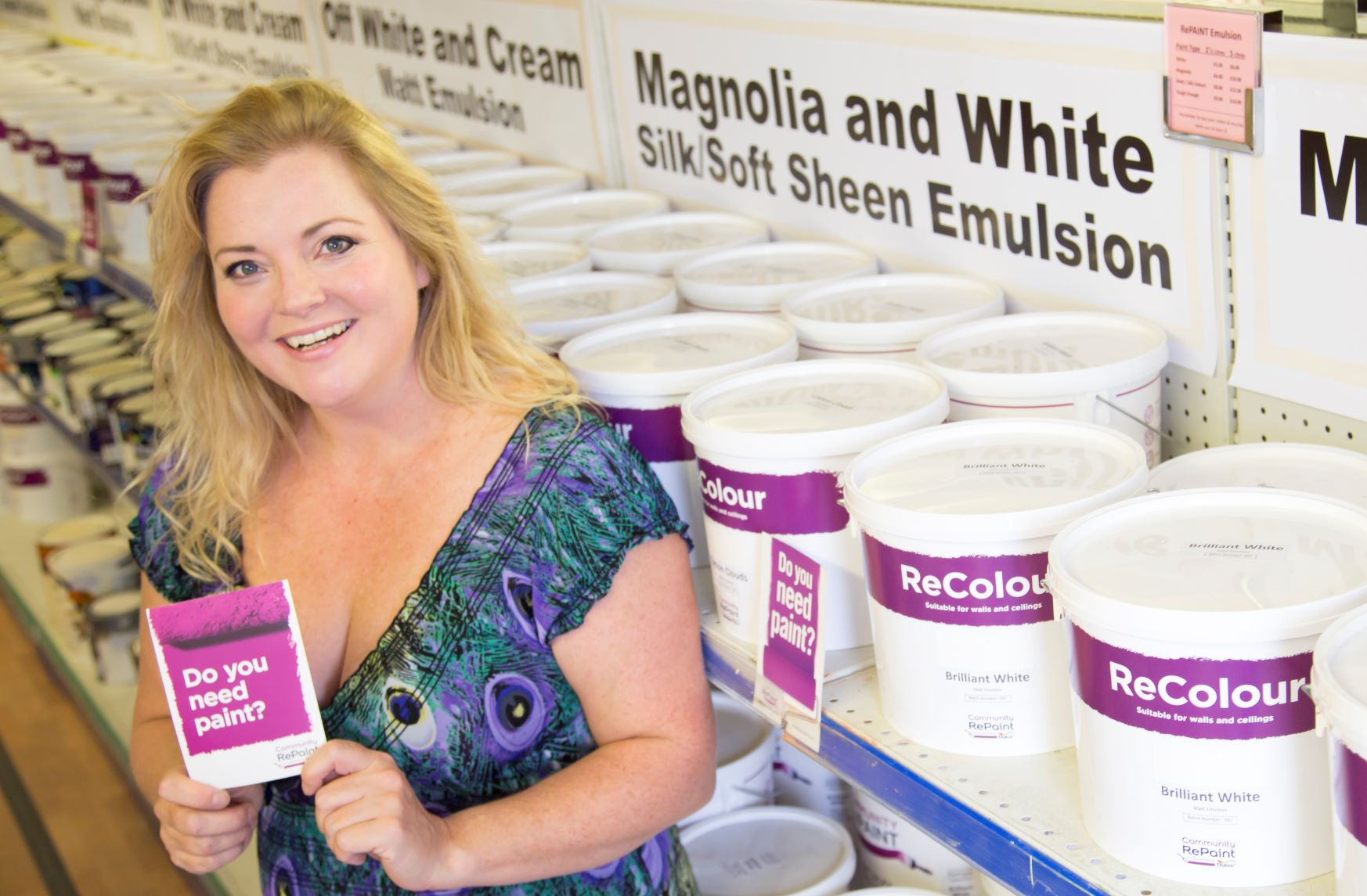 "A photo of a staff member at Community RePaint Cambridgeshire holding a flyer that reads ""do you need paint?"". Behind are two long shelves full of low cost and eco friendly ReColour in silk emulsion, soft sheen emulsion and matt emulsion in off white, white and cream."