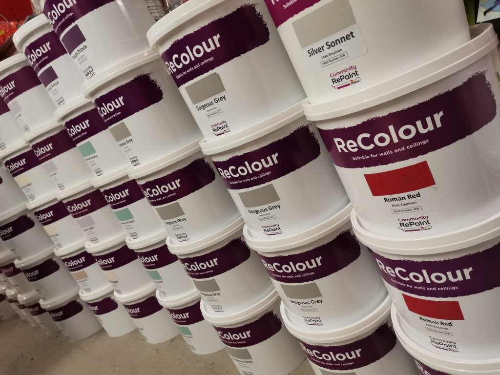 A photo of a range of our low cost and environmentally friendly paint. The ReColour matt emulsion paint and silk emulsion paint is sold in 5 litre plastic containers. There are a range of colour paints on show including Gorgeous Grey, Roman Red and Silver Sonnet.