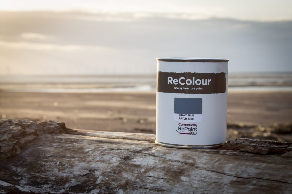 Promotional photo of ReColour chalk paint container with sunset in background.