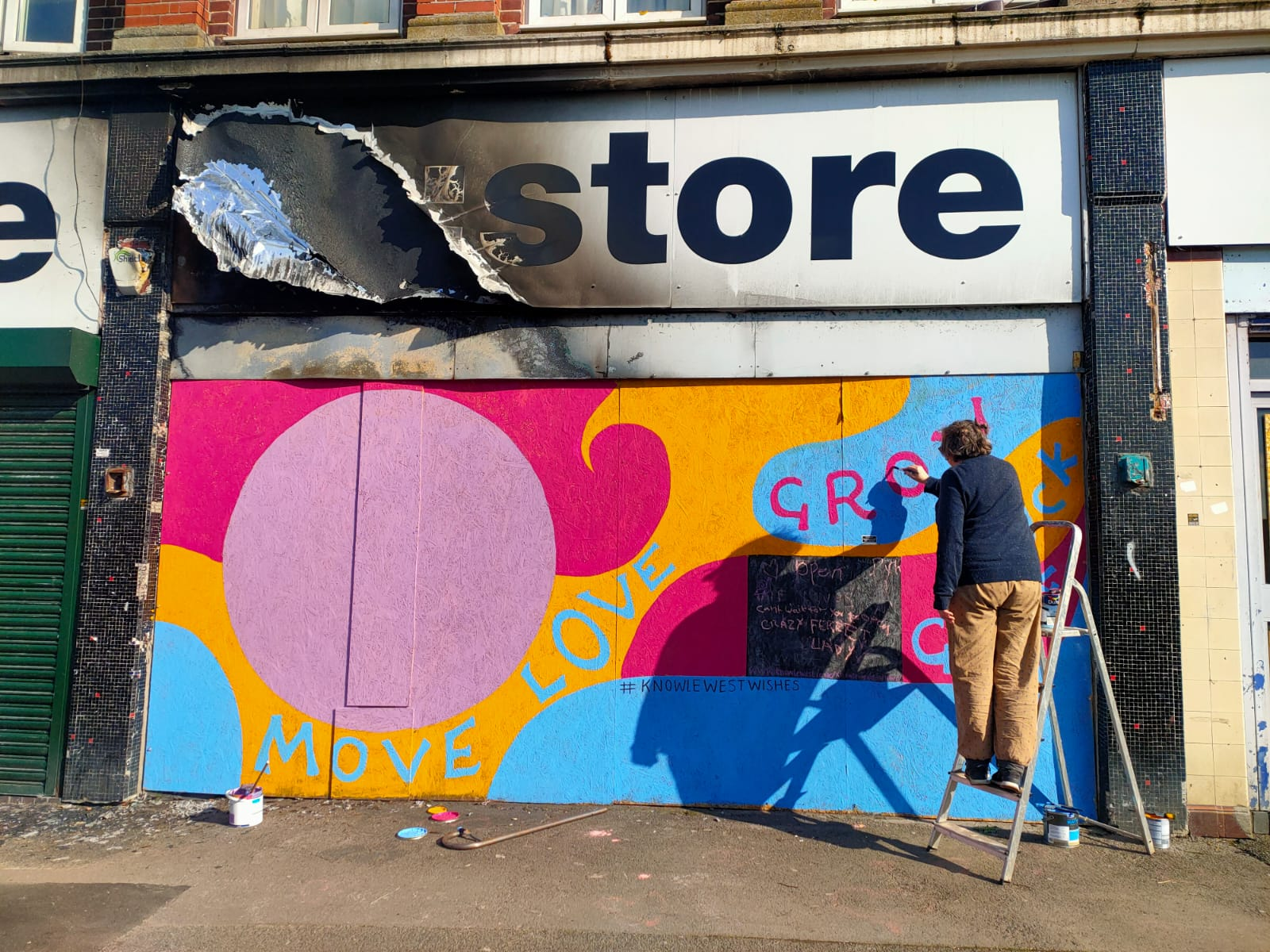 Artist painting the exterior of Community RePaint Bristol South in blue, pink, orange and purple paint.