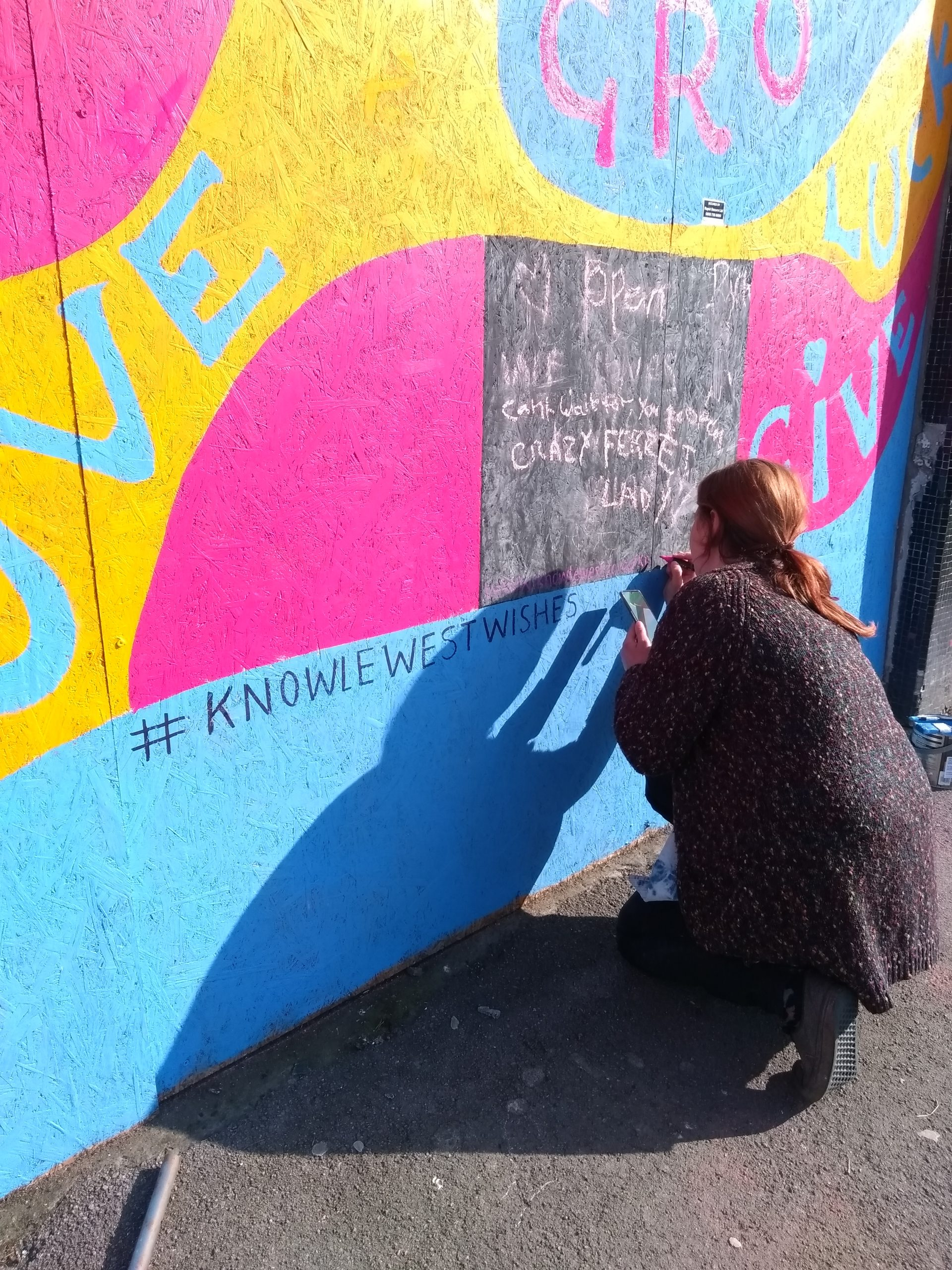 Artist painting the exterior of Community RePaint Bristol South in blue, orange a pink paint.