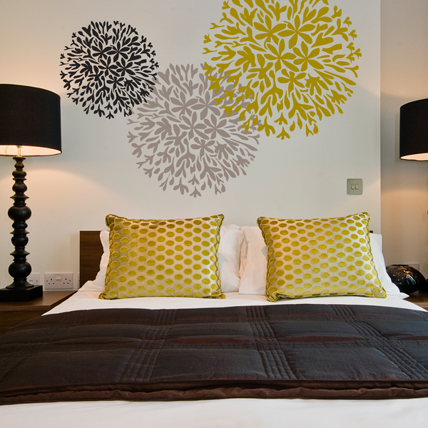 Stenciled flowers painted onto a feature wall in abedroom.