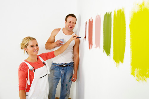 Couple painting swatches on their wall to see which colours work best for the room.
