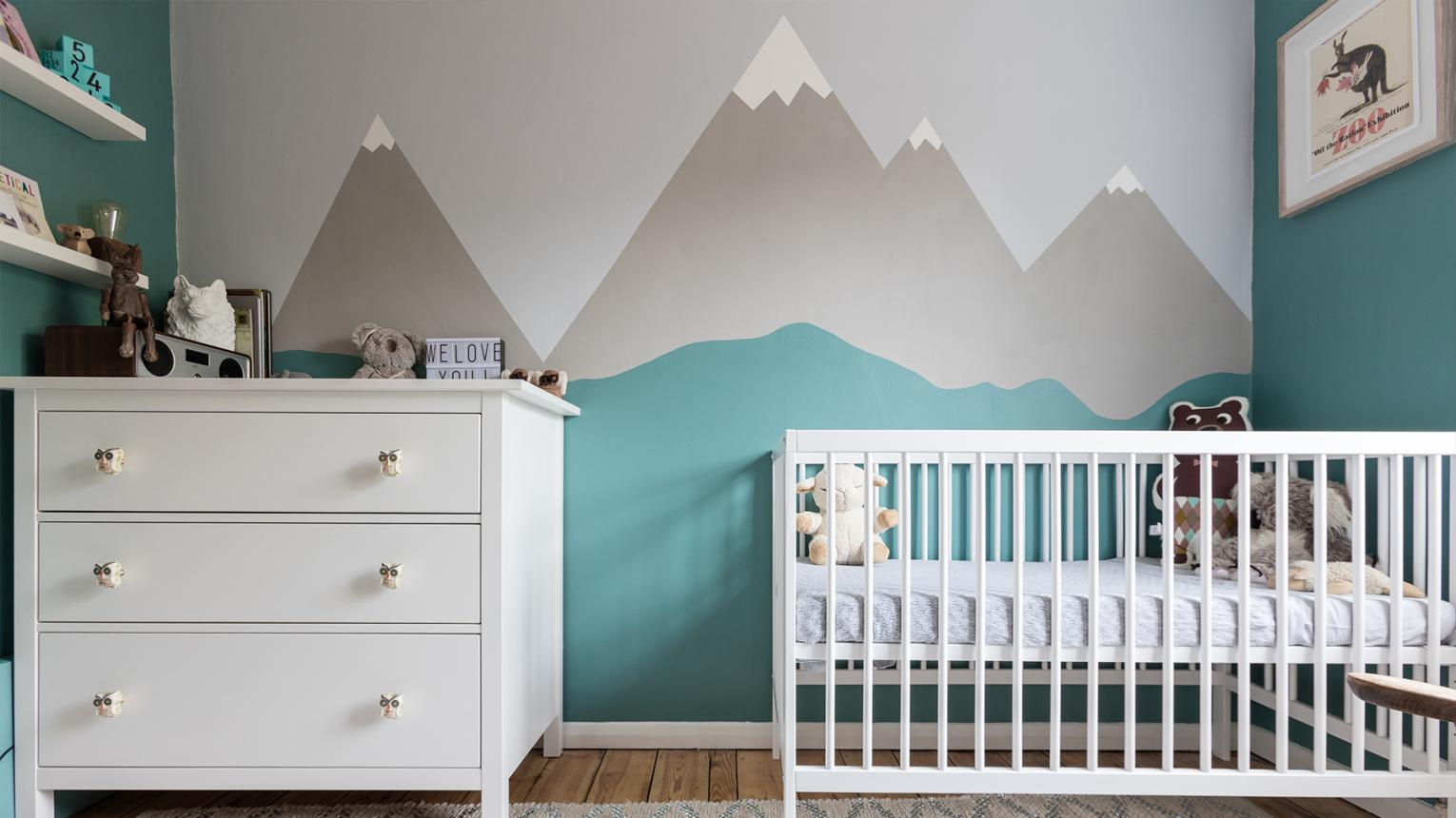 Child's nursery painted in blue throughout apart from one feature wall with a mountain mural.